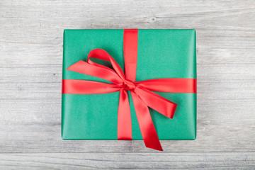 grünes weihnachtsgeschenk auf holzplatte