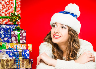 smiling woman looking at presents on a red background