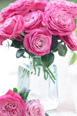 Beautiful fresh pink roses in a vase on a table.