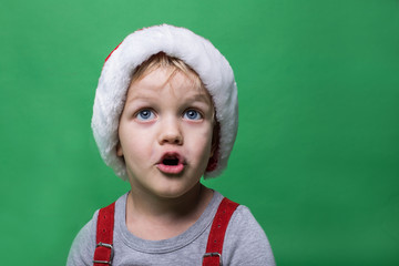 Surprised child with red Santa Claus cap looking up