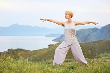 Senior woman doing yoga exercises