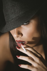 Fashion glamour woman with a cigarette and a hat