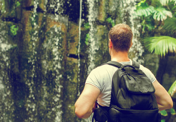 Tourist with backpack near waterfall. Vintage effect. Space for