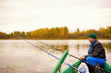 Elderly man fishing on tranquil lake sits in wooden boat
