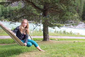 A girl sitting on the hammock. Sjoa kayak camp. Norway.
