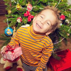 Новогодний портрет счастливого ребенка с подарком .