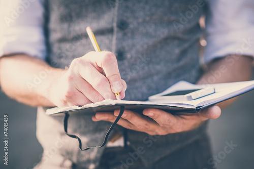 Leinwanddruck Bild close up hands man writing on diary and smartphone
