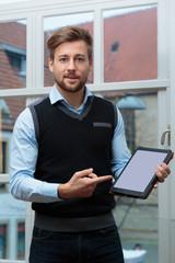 Junger Geschäftmann vor zeigt auf Tablet mit Platz für Text