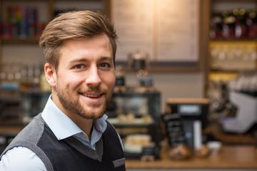 Junger Geschäftmann vor Café Kulisse lachend fröhlich