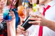 Obrazy na płótnie, fototapety, zdjęcia, fotoobrazy drukowane : Freunde feiern mit Barkeeper in Cocktailbar