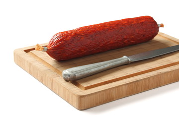Spanish chorizo sausage with knife on wooden board
