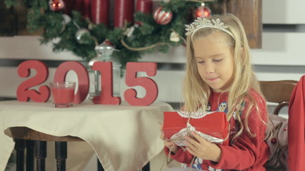 Little blond girl with long hair and wearing a red sweater with