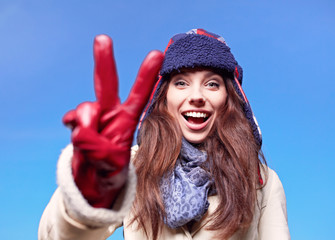 Happy smiling woman with hand sign on winter time
