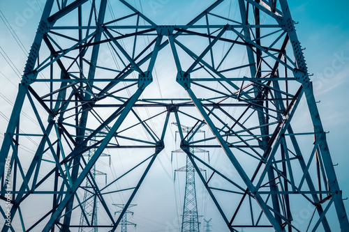 electricity transmission pylon silhouetted - 74018645