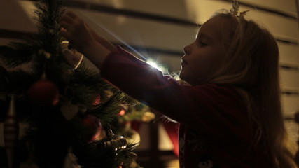 Little blond girl with long hair decorates Christmas tree with