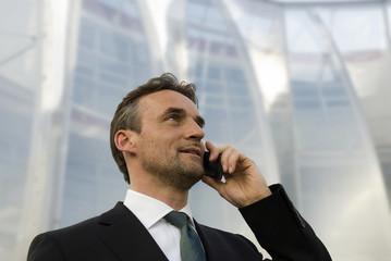 Deutschland, Bayern, Geschäftsmann mit Handy, Portrait