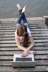 Italien, Gardasee, junge Frau mit Laptop auf Anlegestelle
