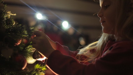 Cute little girl decorates Christmas tree for the New Year