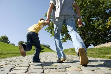 Vater und Sohn laufen, Hände halten, Rückansicht