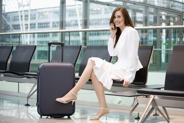 Business-Frau sitzt in Flughafen-Lounge mit Handy, lächelnd