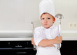 Cross determined little boy chef