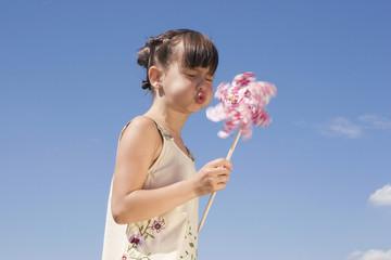 Mädchen bläst Windrädchen, Portrait