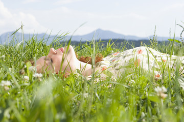 Junge Frau auf der Wiese, die Augen geschlossen