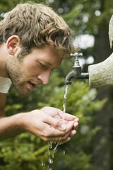 Junger Mann nimmt Wasser aus Brunnen, Seitenansicht