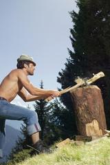 Junger Mann beim Holzhacken, Seitenansicht