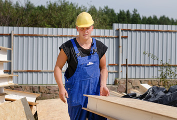 Builder carrying an insulated wooden wall panel