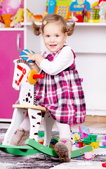 Young girl playing on wooden horse