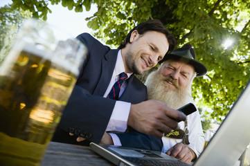 Deutschland, Bayern, Oberbayern, Senioren Bayerische Mann und junger Geschäftsmann mit Laptop im Biergarten