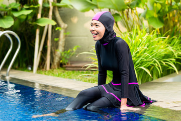 Muslim woman wearing Burkini swimwear at pool