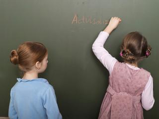 Mädchen stehen vor der Tafel, Schreiben, Rückansicht