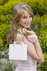Blonde Frau mit Handtasche, lächelnd und fröhlich