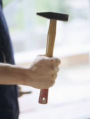 Mann hält Hammer