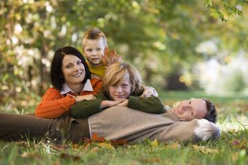 Eltern mit zwei Kindern liegen in der Wiese, lächeln