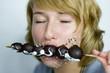 Frau isst Schokoladen-Obst-Spieß, mit geschlossenen Augen