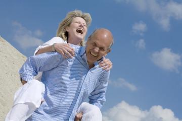 älteres Paar, Senioren, Mann nimmt Frau Huckepack
