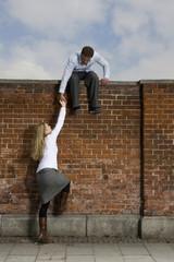 Deutschland, Bayern, München, Junger Mann hilft junger Frau, eine Mauer hoch zu klettern