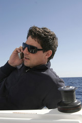 Junger Mann sitzt im Boot, mit Handy