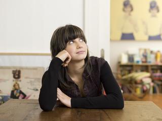 Junge Frau sitzt am Tisch, denkt nach