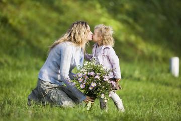 Mutter küssen Tochter, halten Blumenstrauß, Seitenansicht