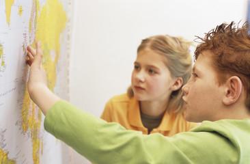 Jungen und Mädchen mit Blick auf atlas, Seitenansicht