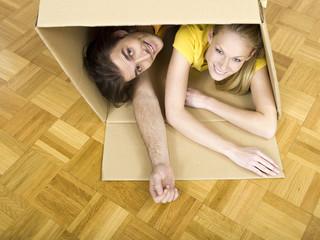 Junges Paar liegen im Karton Umzugskiste