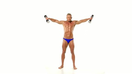 Young athlete trains shoulders silver dumbbells