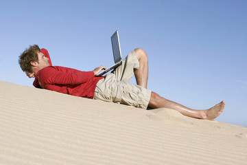 Mann liegt auf einer Düne mit Laptop
