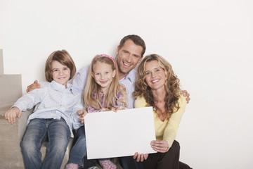 Deutschland, Familie sitzen auf Stufen Treppe mit Laptop, lächeln, Porträt