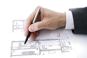 Hand des Mannes zeigt auf Bauplan mit Stift