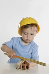 Kleiner Junge trägt Helm und spielt mit Zollstock